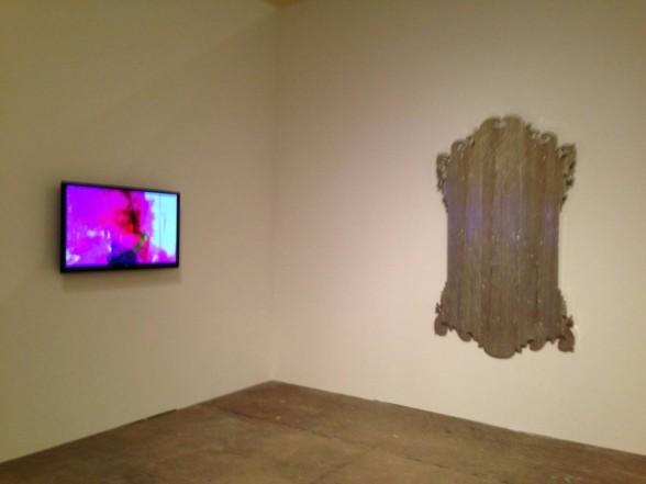 """Eric Abaka """"i'm having my cake and i'm eating cake, 2012 video, 7 minutes (left wall), Virgil Marti, """"Vesper,"""" 2010, Urethane, MDF, plywood and chrome plating, 72x41.5x4"""""""