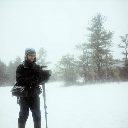 man filming scene in snow