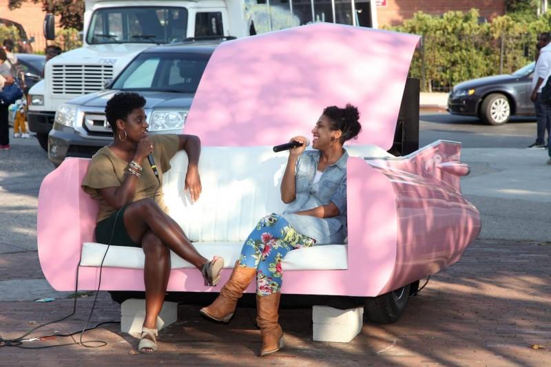 two women talking on pink car