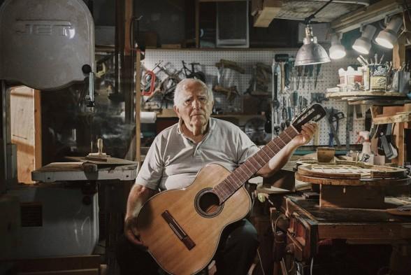 senior citizen holding guitar