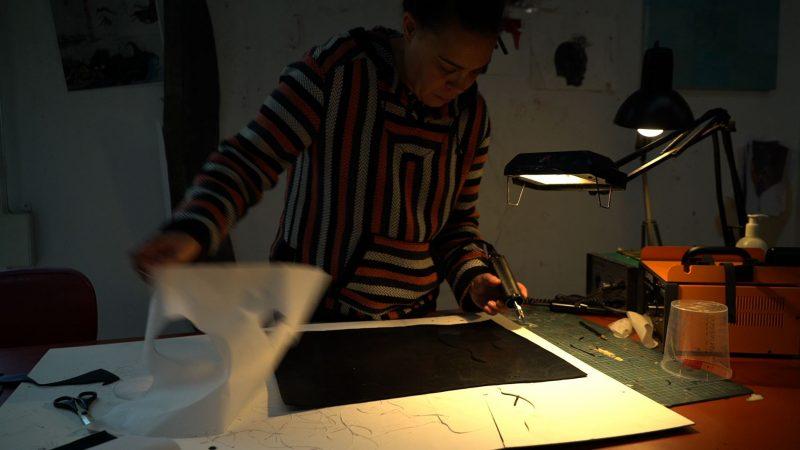 "Ellen Gallagher, working in her studio, featured in ""Black is the Color."""