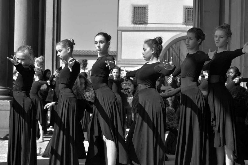 Four girls in long black dresses doing ballet exercises in a straight line outdoors.