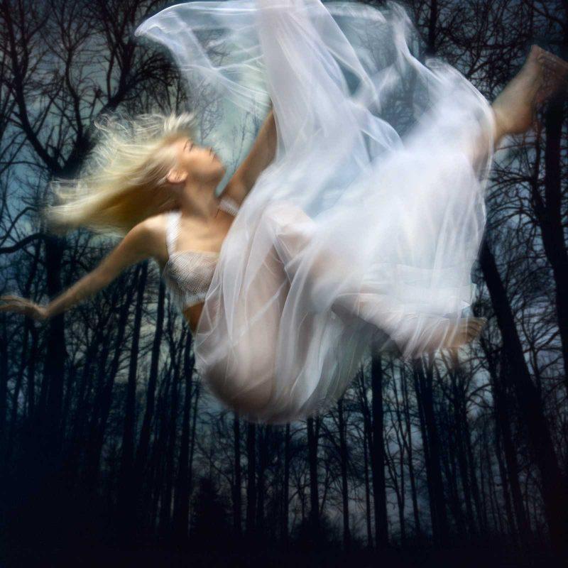 A woman in a white dress falling down through a dark woods.