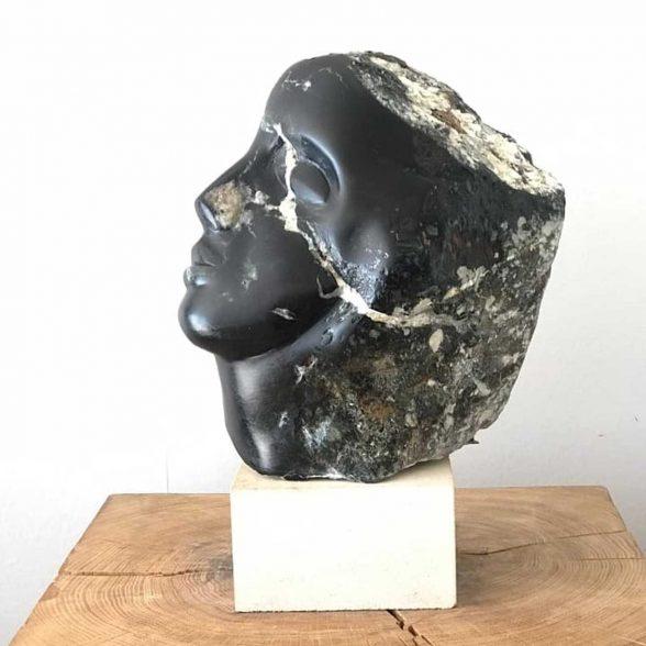 Stone statue of a female facial profile.