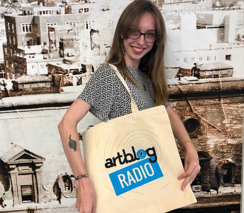 Sydney Cox wearing an Artblog Radio canvas tote