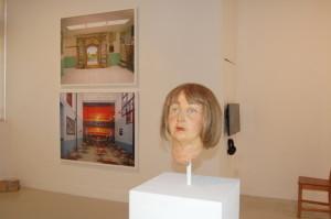 Frank Bender, Anna Duval, fiberglass, clay, paint, wig. Rear left: Alyse Emdur's Prison Landscapes.